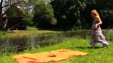 Girl sit on orange rug, fruit grape pear vase near flowing river — Stock Video