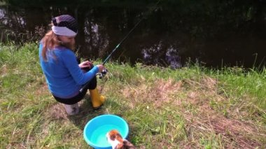 Woman sit on stump near pond, watch playing cat with small fish — Stock Video