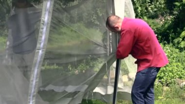 Man bind to arbor bar mosquito screen on windy day, tilt down. — Stock Video