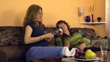 Pregnant woman put blood pressure measure tool on grandma hand — Stock Video