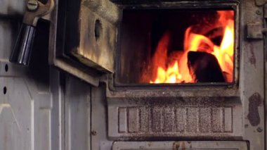 Zoom out of burning wood in stove, woman sit in chair and read — Stock Video