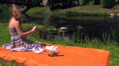 Pregnant woman sit on plaid near river water and fold paper ship — Video Stock