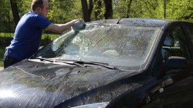 Young man carefully wash his favourite car windscreen and roof — Stock Video