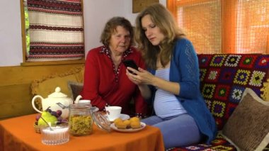 Smiling pregnant granddaughter show mobile phone to grandmother — Vídeo Stock