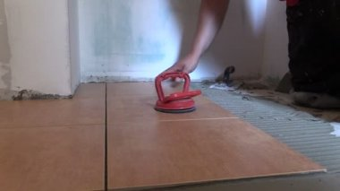 Worker man place floor tiles. Home renovation. Right side slide — Stock Video