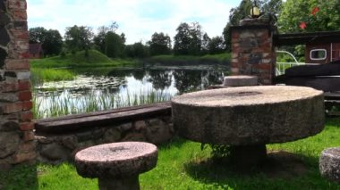 Table and benches made of stone millstone near lake — Stock Video