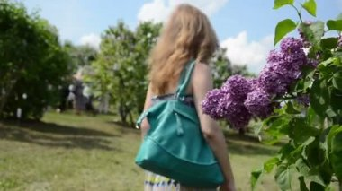 Blooming lilac tree branch and blurred tourist pregnant woman — Stockvideo