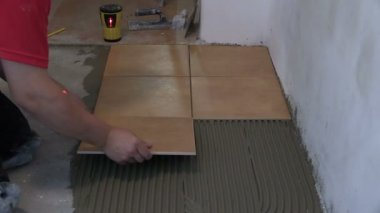 Home improvement, renovation - handyman lay tile on room floor — Stock Video