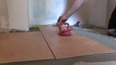 Construction worker man measure and place floor tiles — Stock Video