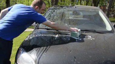 Young man manual clean wash car hood with sponge in garden — Stock Video
