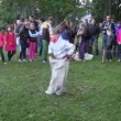 Active children play sack race in city park with people audience — Stock Video #57603765