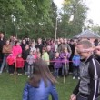 Active children play sack race in city park with people audience — Stock Video #57603803