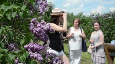 Blooming lilac tree branch and blurr tourist women — Stock Video