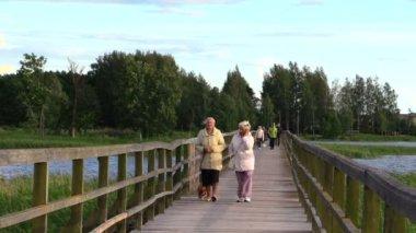 People go long wooden bridge across lake, evening sky light wind — Stock Video