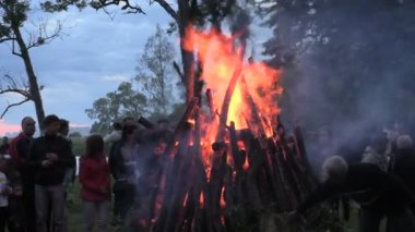 People warm surround big fireplace and celebrate John day — Stock Video
