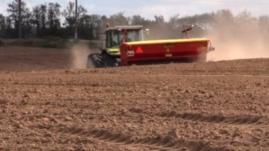 Tractor fertilize soil in field. Time of sowing. Planting crops. — Stock Video