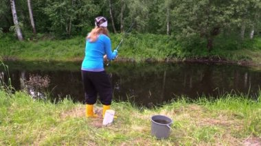 Pregnant woman in yellow boots catch fish. cat sit near bucket — Stock Video