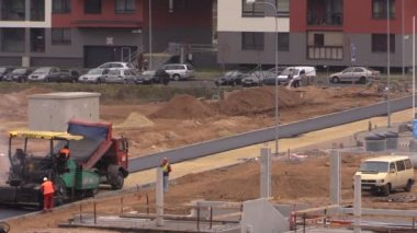 Workers with heavy machines pave asphalt near residential houses — Stock Video