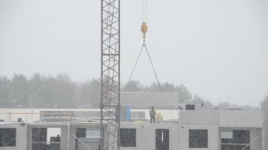 Crane lifting house part and builders workers on flat house roof — Stock Video