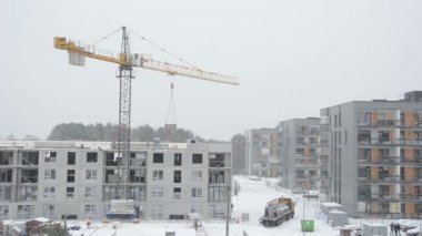 Crane lift concrete house part and workers work in snow fall — Stock Video
