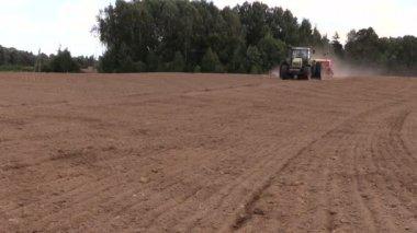 Tractor spread fertilizer on cultivated field in summer — Vidéo