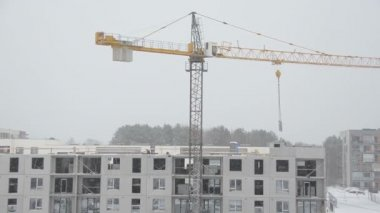 Crane lift block house part and builders work in heavy snow fall — Stock Video