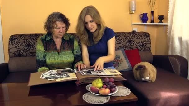 Granny ver álbum de fotos viejo blanco negro con su nieta — Vídeo de stock