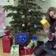 Joyful woman show her lovely baby gift box near Christmas tree — Wideo stockowe #68573405