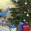 Mother with newborn baby in her hands hang Christmas tree toy — Stock Video #68573445