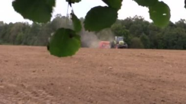 Tree branch with leaves move and tractor fertilize sow field — Stock Video