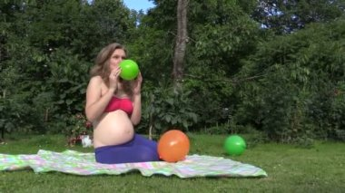 Cute pregnant woman girl inflate colorful balloon in garden — Stock Video