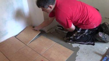 Construction worker tiler place floor tiles. Left side sliding — Stock Video