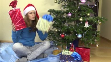 Female girl check shake gift present boxes near Christmas tree — Stock Video