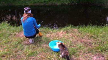 Cat with claw catch fish from bowl, woman fishing at pond — Stock Video