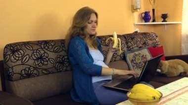 Pregnant girl eat banana work with computer and caress belly — Stock Video