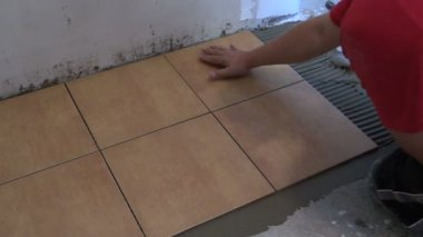 Handyman lay floor tiles at home. Closeup shot — Stock Video