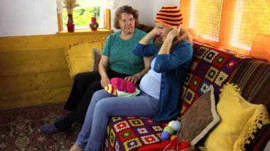 Grandmother with pregnant granddaughter size handmade wool cap — Stock Video