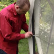 Zoom out man tie protective tent bower net to construction — Stock Video #70644375