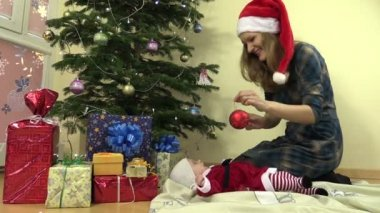 Mother hang christmas tree toy. infant baby in christmas dress — Stock Video