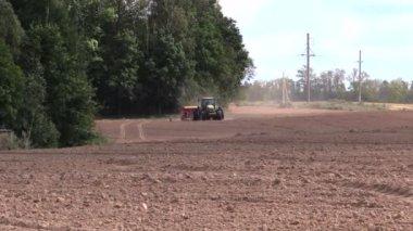 Tractor spread fertilizer on cultivated field in autumn — Stock Video