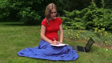 Pregnant woman look at laptop computer and write on notebook — Stock Video