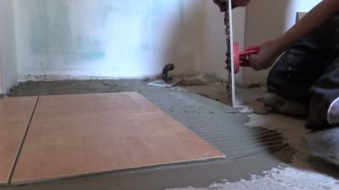 Handyman worker place floor tiles with special tool — Stock Video