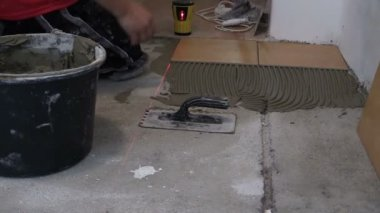 Zoom in man straighten tile on cement surface with laser gear — Stock Video