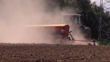 Dust rising from tractor fertilizer prepare soil in field — Stock Video