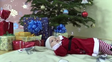 Lovely baby girl lie near christmas tree and gift present boxes — Stock Video