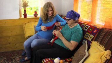 Pregnant women look grandma knitted socks sit on sofa and talk — Stockvideo