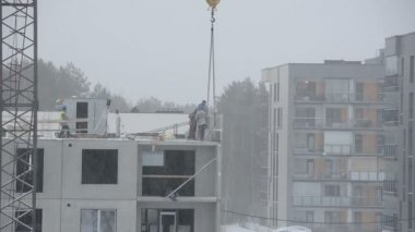 Snow fall and construction site workers build house in winter — Stock Video