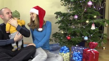Family father and mother kiss newborn baby daughter in Christmas — Stock Video