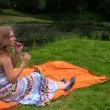 Woman drink cider champagne alcohol sitting on plaid near river — Stock Video #72743593