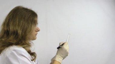 Lab vrouw schrijven van nummers op de kolf en zet in poppy plant — Stockvideo